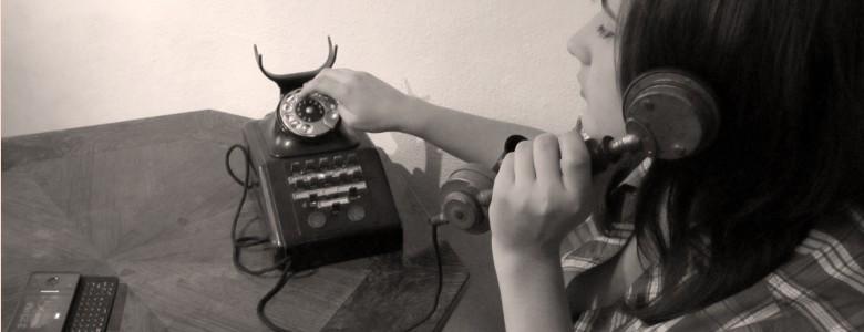 Mensch mit alter Telefonapparat, daneben ein Smartphone auf dem Tisch