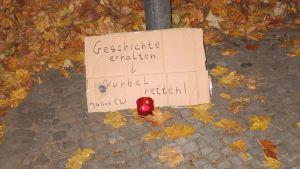 """Das Foto zeigt ein handgemaltes Plakat """"Geschichte erhalten – Kurbel retten"""" der Jusos CW vor dem Kino """"Die Kurbel"""" mit Teelicht."""