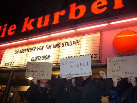 Das Foto zeigt drei Demonstranten vor dem Kino Die Kurbel, die für dessen Erhalt demonstrieren.