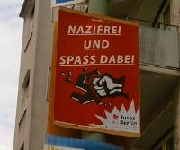Plakat 'Nazifrei und Spaß dabei' von Jusos Berlin, Motiv: Hakenkreuz zerschlagende Hand; Hintergrund rot; vor Häuserwand